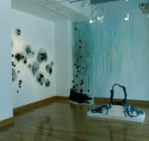 """Concurrent"" Artist Residence Culminating Exhibition, 2009 @ Craft Alliance's Grand Center Installation space. Piece on left wall: ""Drops"", sanded and shaped plexi-glas with clay forms.  Right Wall piece:  ""Run-Off"".  Ink and Clay.  Piece on floor: ""Oil and Water"", ceramic."